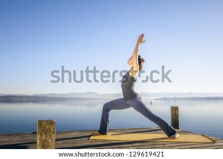 An image of a pretty woman doing yoga at the lake - Virabhadrasana - stock photo