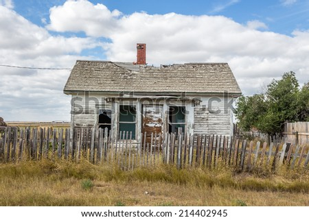 an image of a quaint little abandoned house with a broken down wooden fence under a beautiful blue sky with white clouds - stock photo