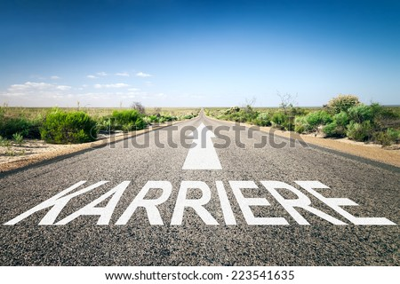 An image of a road to the horizon with text career in german language - stock photo