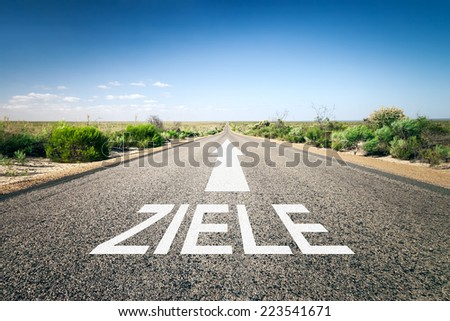 An image of a road to the horizon with text goals in german language - stock photo