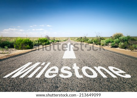 An image of a road to the horizon with text milestone - stock photo