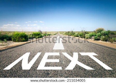 An image of a road to the horizon with text next - stock photo