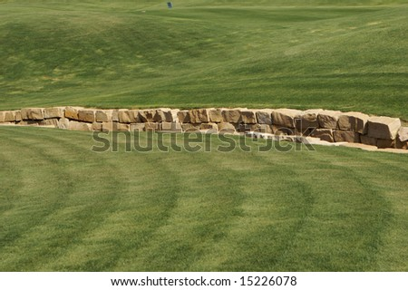 An image of a rock wall in a golf course - stock photo