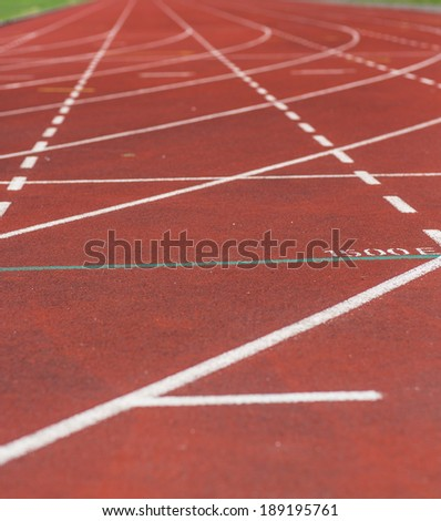 An image of a running track. Image taken outdoor on a partly cloudy day.