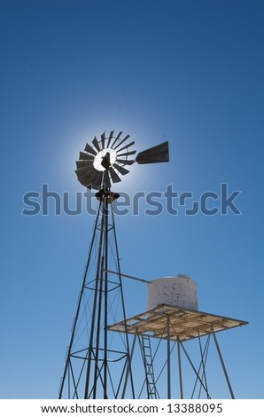An image of a rural windmill in a blue sky