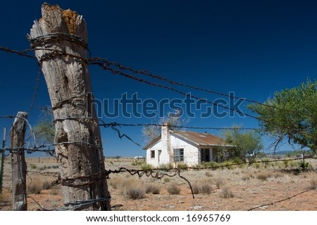 An image of a rustic country home surrounded by barbed wire fencing