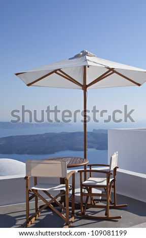 an image of a set of table and chairs on a balcony overlooking the caldera. Santorini, Greece. - stock photo