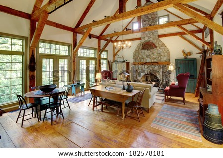 An image of a sitting room and fireplace in a primitive colonial style reproduction home. The home is built with materials reclaimed from structures built in the late 1700's. - stock photo
