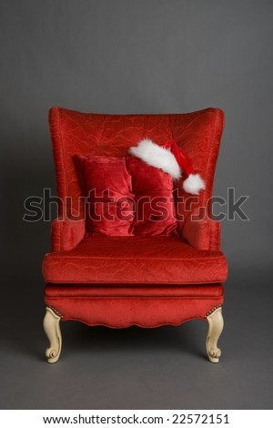 An image of a solitary bright red chair with a santa hat - stock photo