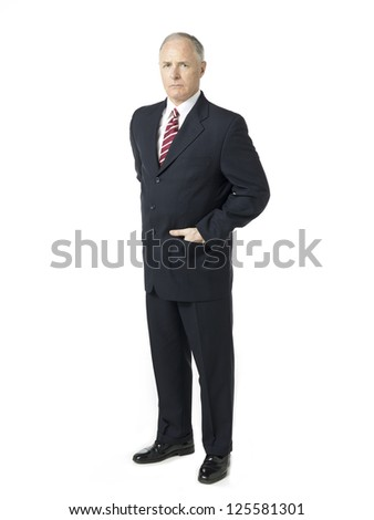 An image of a standing businessman with his right hand on his coat's pocket