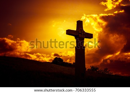 An image of a stone cross in front of a dramatic evening sky