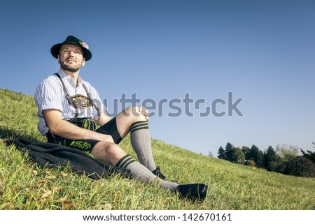 An image of a traditional bavarian man relaxing in the grass - stock photo