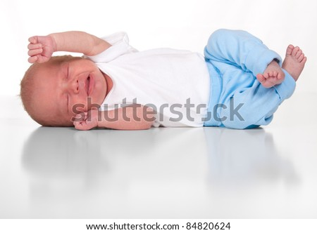 An image of a two week old baby boy with the reflection in black and white.  Image is isolated on white with reflection.