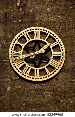 an image of a very old bronze clock on an old wall with lichen attached. - stock photo