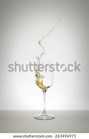 An image of a white wine splash in the glass - stock photo