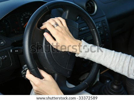 An image of a woman  driving playing the horn