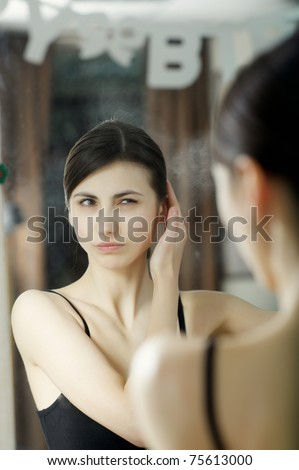 An image of a woman looking at herself in the mirror - stock photo