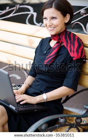 An image of a woman with a  laptop on the bench