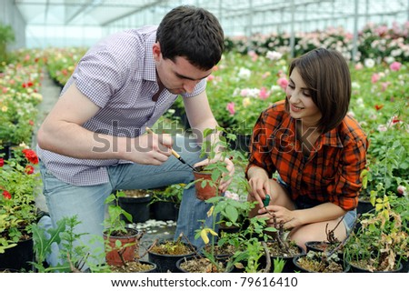 An image of a young couple in a greenhouse - stock photo