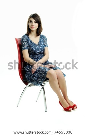 An image of a young elegant girl sitting on a chair - stock photo