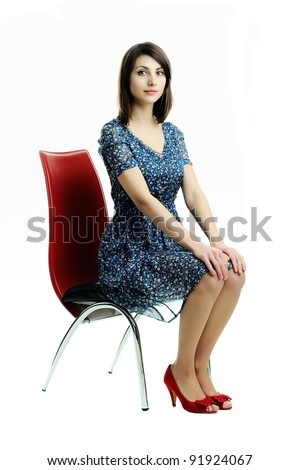 An image of a young girl sitting on a chair - stock photo