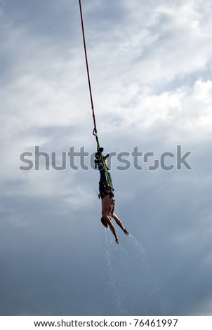 an image of an action sports thrill seeker after jumping from a bungee platform. - stock photo
