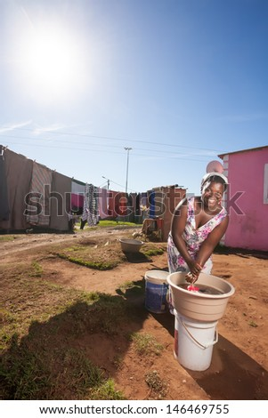an image of an african woman doing her laundry in the township with only a single bucket of water smiling brightly - stock photo