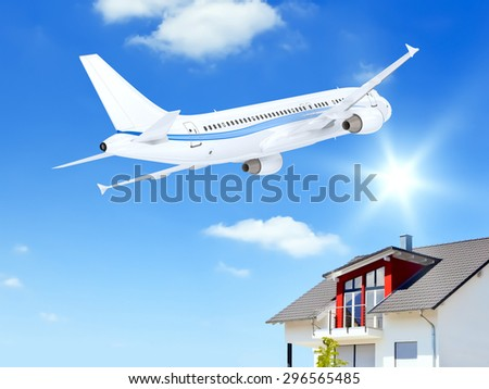 An image of an airplane over a private house - stock photo