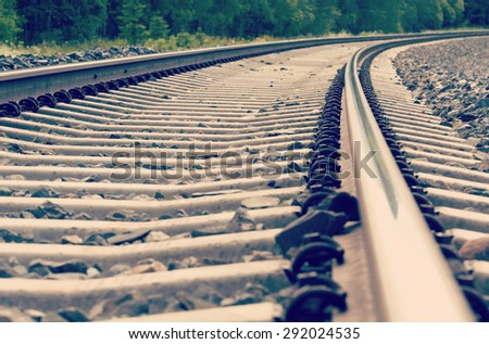 An image of an empty railroad track. The track is turning right and the image has a vintage effect. - stock photo