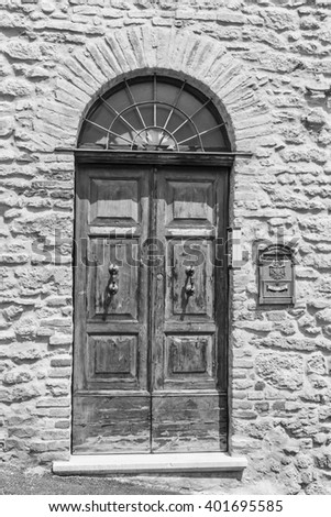 An image of an old door in Italy.Black and white photography. - stock photo