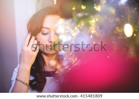 An image of beautiful young woman stands against christmas tree