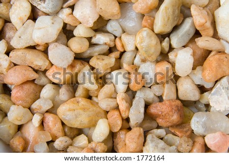 An image of beige colored pea gravel for use as a background texture, wallpaper or layer - stock photo