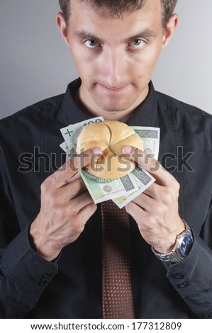an image of businessman is eating a sandwich with money