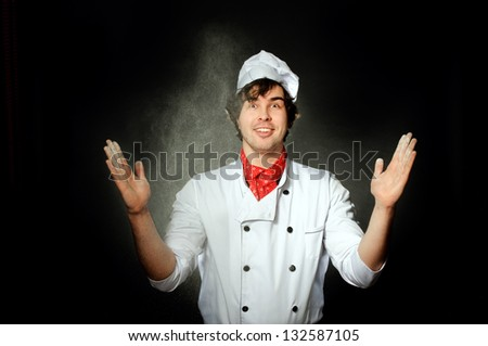 An image of cook scatters flour on grey background - stock photo