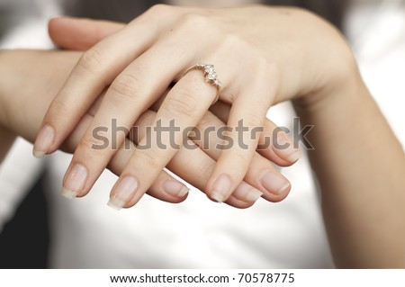 an image of engagement ring inserted into finger - stock photo