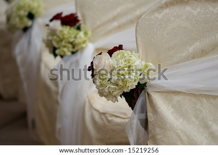 An image of floral arrangements located on seats at a wedding ceremony - stock photo