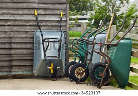 An image of four Wheelbarrows and other various garden tools leaning against a shed and fence on a hard standing. - stock photo