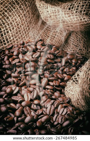 An image of freshly roasted dark coffee beans with a photographic filter desaturating the colors and emphasizing the rustic nature of the iamge - stock photo