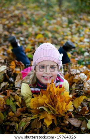 An image of girl in leaves in autumn park