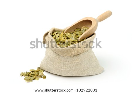 An image of green pumpkin seeds in a burlap sack - stock photo