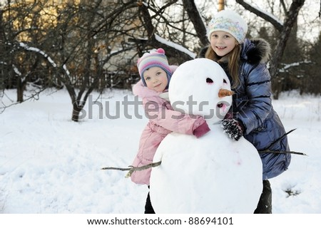 An image of happy sisters posing with snowman - stock photo