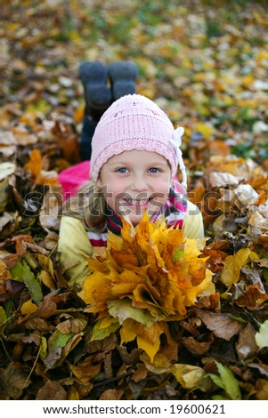 An image of little girl with yellow leaves in autumn park
