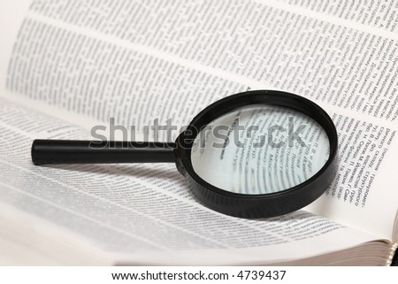 An image of magnifier and book