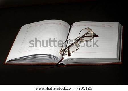 An image of notebook and glasses