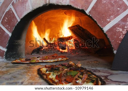 an image of pizza in a wood burning oven - stock photo