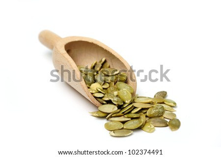 An image of pumpkin seeds in a wooden scoop - stock photo