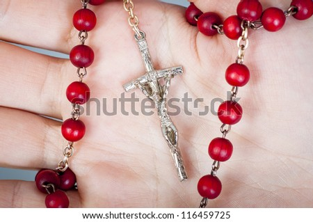 an image of rosary on female hand - stock photo
