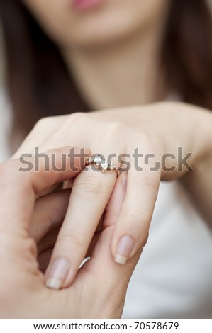 an image of situation of inserting engagement ring into a finger
