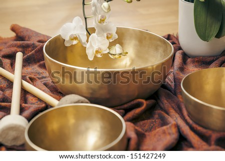 An image of some singing bowls and a white orchid - stock photo