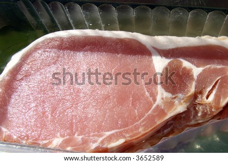 An image of some sliced bacon within its package. - stock photo